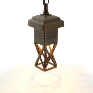 VOLT® Locket mini brass hanging light illuminated.