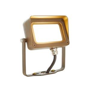 VOLT® 12W integrated LED brass flood light with yoke mount illuminated.